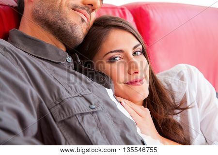 Portrait of young woman with boyfriend. Affectionate couple is relaxing on sofa. Male and female partners are spending leisure time.
