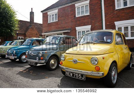 AMERSHAM, UK - SEPTEMBER 13: A line-up of old and new iconic Fiat 500 motorcars are placed on public display at the Amersham Heritage Day festival on September 13, 2015 in Amersham.