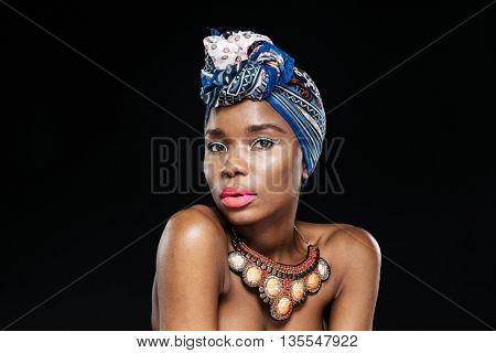 Close-up portrait of an attractive afro american woman looking at camera isolated on the black background
