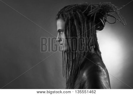 Young man's portrait. Stylish handsome sexy Guy with Dreadlocks in black leather fashionable jacket Close-up face. Tribal Style. Trendy youthful man's look