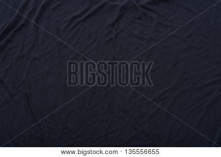 Close up of wrinkled black color fabric bed sheet texture background.
