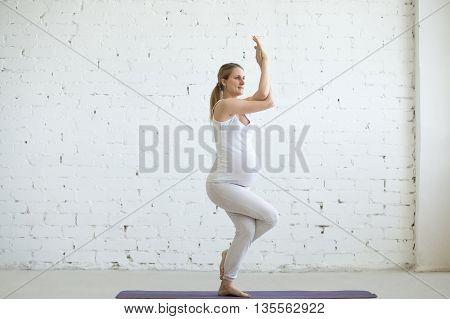 Pregnant Young Woman Doing Prenatal Yoga. Eagle Pose