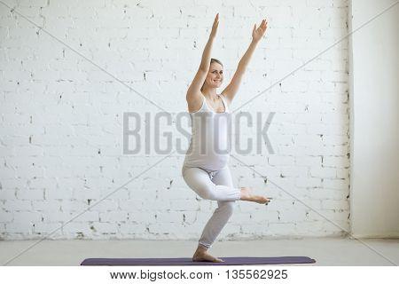 Pregnant Young Woman Doing Prenatal Yoga. Chair Pose, Utkatasana