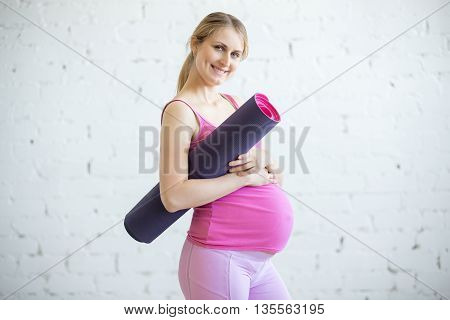 Smiling Beautiful Pregnant Young Woman Holding Fitness Mat