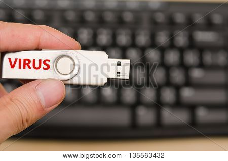USB virus thumb drive or virus USB stick with hand holding on keyboard background