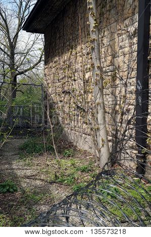 The exterior of the visitor's center of the old Illinois State Penitentiary, now vacant, abandoned, and overgrown with weeds.