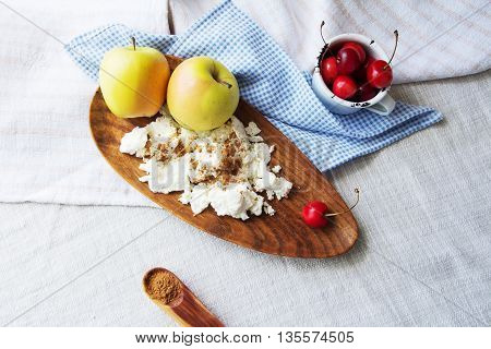 Composition of fruits and berries, cottage cheese. Reason for the longevity is apples, cherries. Fruits and berries, cottage cheese in a bowl on a checkered napkin on the table.