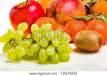 Fresh juicy fruit - bunches of grapes, mandarin, apple. Fresh juicy fruit - still life