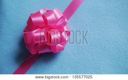 Pink Loopy Bow ribbon on blue fabric background