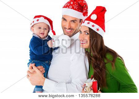 Portrait of happy parents with baby boy. Family of three are wearing Santa hats. They are in casuals isolated over white background.