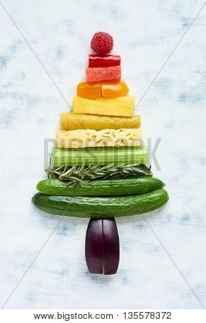 Arrangement of assorted fruit and vegetables in rainbow gradient in shape of a triangle, tree, pyramid, eat healthy during festive holidays concept