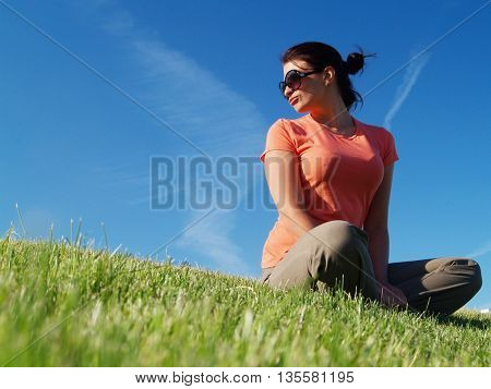 Woman wearing sunglasses relaxing in the sun lying sprawled out on the green grass