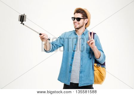Cheerful young man with backpack taking pictures with mobile phone and selfie stick