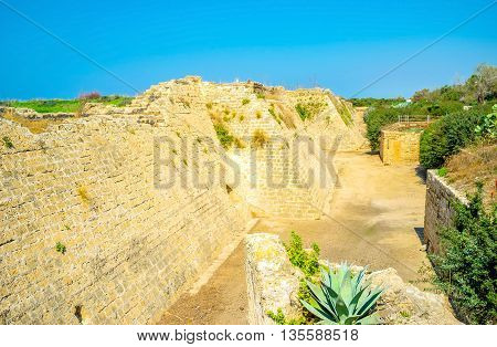 The ramparts of the Crusader fortress surrounded by the dug moat in Caesarea Israel.