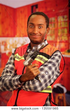 Young engineer carpenter wearing square pattern flanel shirt with red safety vest, holding handheld electric power tool smiling to camera.