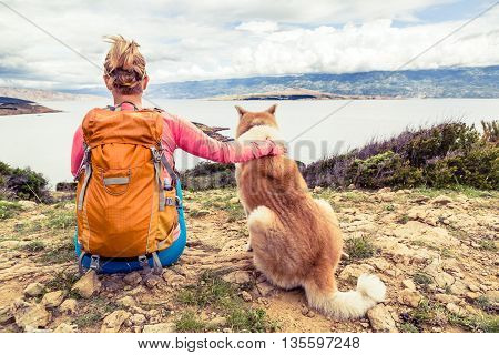 Woman hiker looking at sea with akita inu dog on seaside trail. Recreation and healthy lifestyle outdoors in summer mountains and sea nature. Beautiful inspirational landscape trekking and activity.