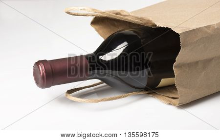 A bottle of red wine in a paper bag perhaps being given as a gift or bought at a liquor store on a white background with reflection and shadow