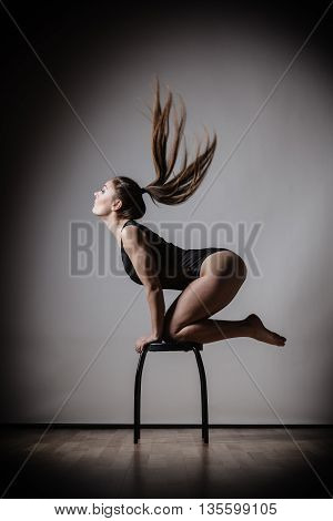 Bodybuilding. Atletic woman fit slim body posing with hair blowing on dark background