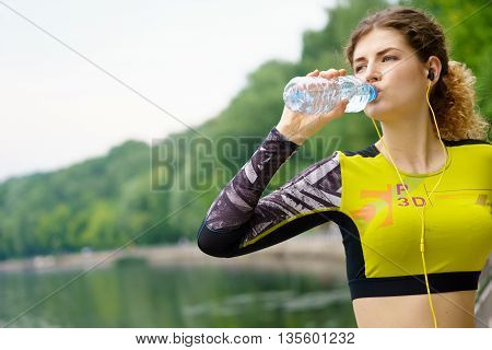 Beautiful athlete caucasian woman in sportswear and headphones drinking water in park