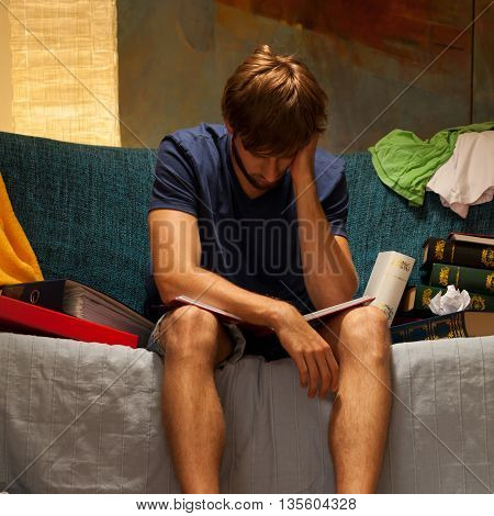 Sleepy student sitting at sofa before examination poster