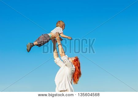 Beautiful Red-haired Mother Playing With Her Baby.