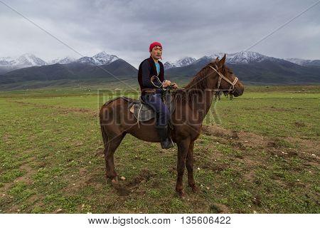 ISSYK KUL, KYRGYZSTAN - MAY 28, 2016: Nomadic horseman looks at me during the traditional horse games, Ulak Tartysh in Issyk Kul Lake, Kyrgyzstan.