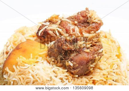 Mutton Lamb kacchi biryani with chili and life on white plate background