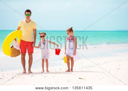 Young happy father and little daughters having fun on white beach in sunny day