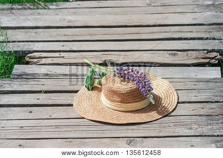 Straw hat with lupin flower on the plank footway among the grass.