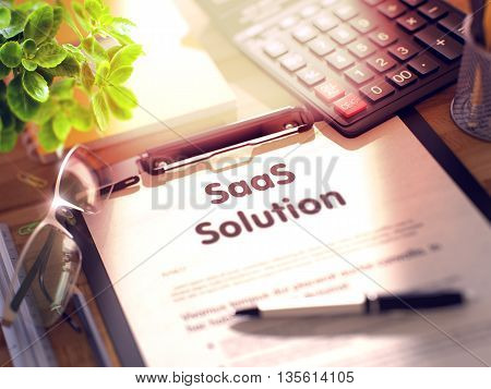 Clipboard with Concept - SaaS Solution with Office Supplies Around. SaaS Solution- Text on Paper Sheet on Clipboard and Stationery on Office Desk. 3d Rendering. Blurred Illustration.