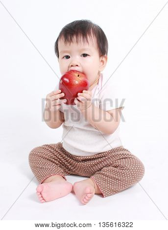 Cute baby with red apple (eating healthy food) on white background.