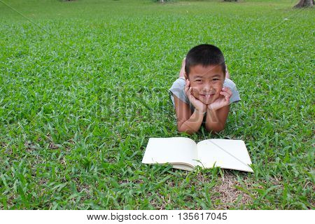 Young boy reading in the park, spring time.