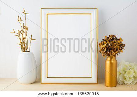 White frame mockup with white and golden vases. Portrait or poster white frame mockup. Empty white frame mockup for design presentation.