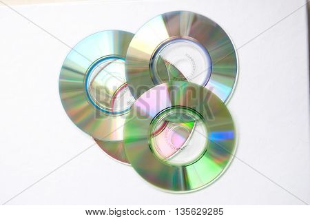 four silver Cd's on white background, top view