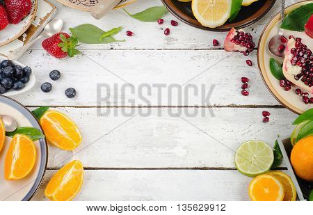Citrus Fruits And Berries On A White Wooden Background.