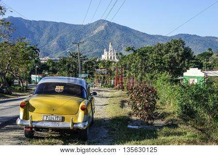 Trinidad Cuba - January 12 2016: The road to the Shrine Basilica Maria la Virgen della Caridad del Cobre. In the foreground holding an old American antique car and in the background is the pilgrimage site of the Lady of Charity of El Cobre in Santiago de