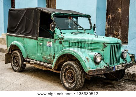 Santiago de Cuba Cuba - January 13 2016: Typical scene of one of streets in the center of Santiago de cuba - Colorful architecture old vintage green car. Santiago is the 2nd largest city in Cuba