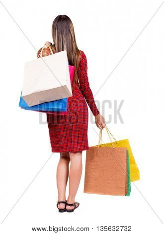 back view of woman with shopping bags .  Isolated over white background. The girl in red plaid dress standing throwing shoulder purchase.