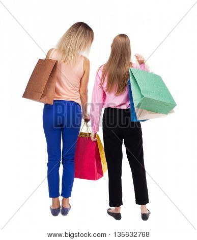 back view of  two women  with shopping bags. backside view of person.  Rear view people collection. Isolated over white background. Two girls with bags stand next procurement.