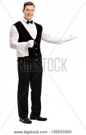 Full length portrait of a friendly waiter greeting someone isolated on white background