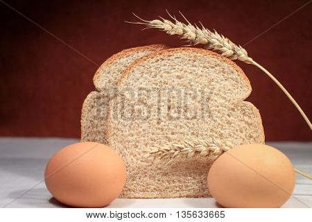 Slices of whole wheat bread with eggs and wheat.
