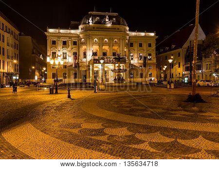 BRATISLAVA SLOVAKIA - 29th April 2016: The outside of the Historical building of the Slovak National Theatre at night. People can be seen.
