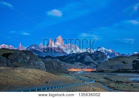 Amazing Patagonia in February. The valley of town of El Chalten.  The white top of Fitzroy rocks and village of El Chalten at dusk