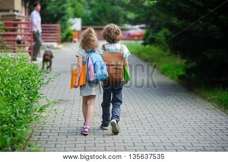 Two pupils of primary school go hand in hand. Boy and girl with school bags behind the back. Beginning of school lessons. Warm day of fall.