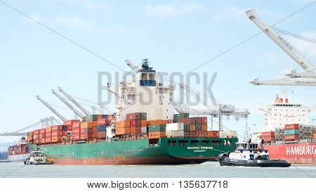 Oakland CA - June 09 2016: Cargo Ship SEASPAN HAMBURG with tugboats assisting the vessel to maneuver into the Port of Oakland the fifth busiest port in the United States.