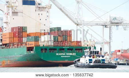 Oakland CA - June 09 2016: Tugboat AHBRA FRANCO at the stern of Cargo Ship SEASPAN HAMBURG assisting the vessel to maneuver into the Port of Oakland.