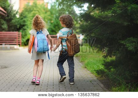 Young students boy and girl going to school. They hold hands. They hold hands. Children behind shoulders have satchels. Warm day in an early autumn.
