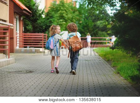Boy and gerlie go to school having joined hands. Warm September day. Good mood. Behind backs at children satchels. The little girl laughs.