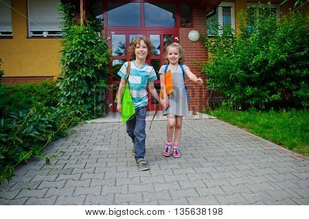 Boy and girl go on a schoolyard having joined hands. They are pupils of elementary school. School friends. To children it is cheerful. Sunny day.