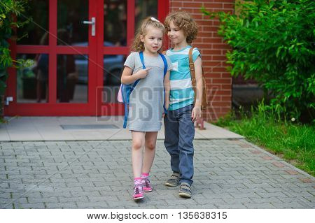 Boy and girl go to school having joined hands. Warm September day. Good mood. School students about something talk. On faces lovely smiles.